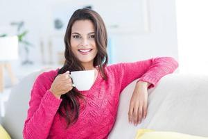 sonriente hermosa morena descansando en el sofá y sosteniendo la taza
