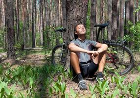 Relaxing bicyclist in coniferous forest the spring under pine tree photo