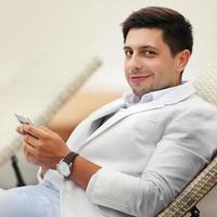 Happy relaxed  groom in white suit sitting near bench at photo