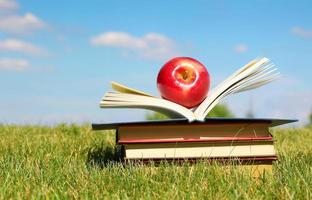 De vuelta a la escuela. libro abierto y manzana sobre hierba foto