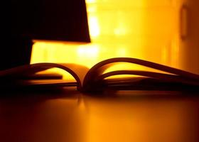 Long exposure shot of open book in reflected candle light photo