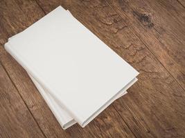 plantilla de maqueta de libro blanco vacío sobre fondo de madera