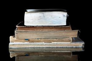 pila de libros antiguos con páginas vintage reflejadas