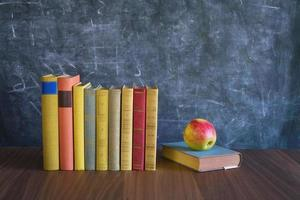 books and apple in front of a black board