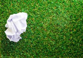 Crumpled paper on Green grass background