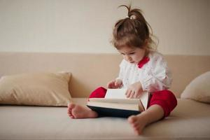 little girl reading book at home photo
