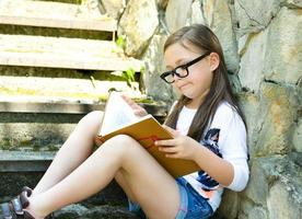 Little girl is reading a book outdoors photo