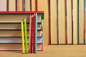 pilha de livros e lápis de cor numa superfície de madeira.