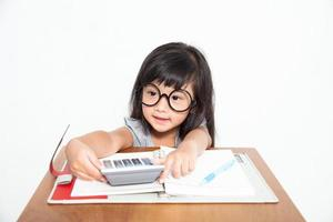 Niña asiática estudiante con cuaderno y calculadora aislar