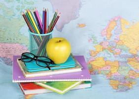 De vuelta a la escuela. una manzana, lapices, vasos y libros foto