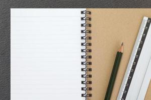 Open notebook and pencil on black table background