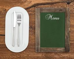 chalkboard with white plate, knife and fork
