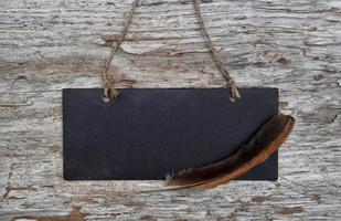Chalkboard with feather on the old wood photo