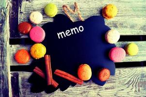 Colorful macaroons with chalk board on a wooden background photo