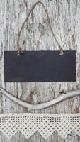 Chalkboard with lacy ribbon and dry branch on old wood photo