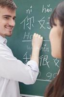 Smiling male teacher with student in front of chalkboard writing