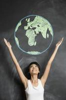 Woman reaching arms towards a chalkboard earth drawing