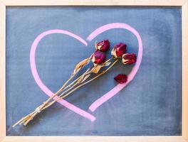 Rosas secas en una pizarra con corazón dibujado