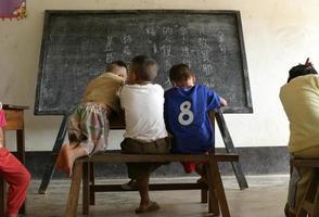 Grupo de niños chinos en la escuela frente a una pizarra