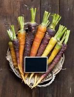 Fresh organic rainbow carrots and a small chalkboard