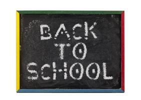 regreso a la escuela escrito en pizarra de estudiantes pequeños