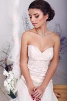 joven novia en traje de novia sentado en columpio en studio foto
