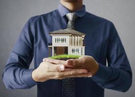 Businessman holding house model photo
