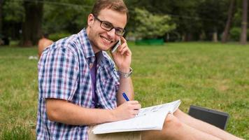 Casual man studying outdoors with a notebook.