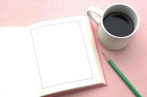 Opened book and cup of coffee on pink background