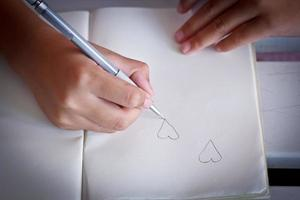 Children drawing a heart shap on her note book. photo