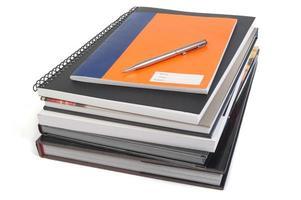 libros de referencia, cuadernos y bolígrafo