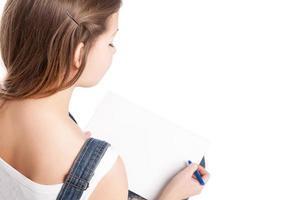 mujer joven dibujando en su cuaderno de notas. vista trasera foto