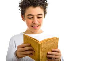 chico lindo lee libro en blanco de corcho marrón sonriendo foto