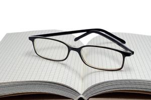 book and glasses isolated on white background photo
