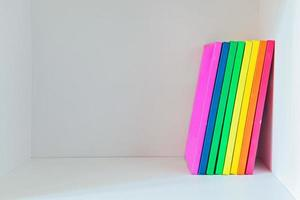 Multi colored books on the light-coloured bookshelf