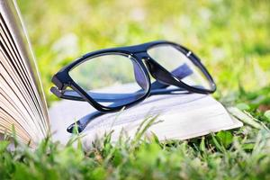 An open book with glasses on a meadow photo