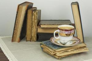 Porcelain cup of coffee and old books