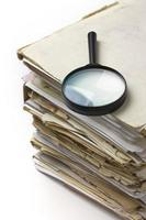 Magnifying lens  on the stack of old paper files photo