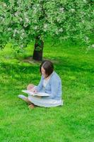 Young woman reads a book under blooming tree photo