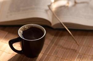 taza de café, de pie junto a un libro abierto foto