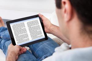 Hombre con dispositivo de pantalla táctil que muestra un libro electrónico foto