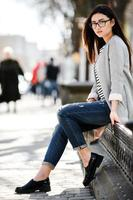 Beautiful fashion model in glasses sits photo