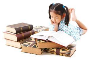 Aziatische schattig meisje leesboek terwijl vast op de vloer.
