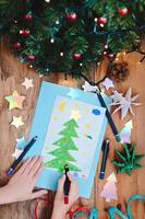 Niña dibujando tarjetas de Navidad con pino foto