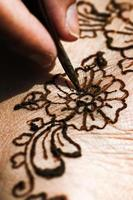 Henna tattoo drawing with herbal dye on foot floral design photo