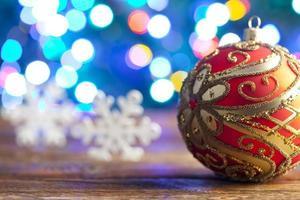 Adorno de navidad y copos de nieve sobre fondo de iluminación