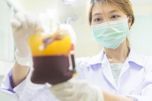 asia woman scientist working with device for blood analysis photo