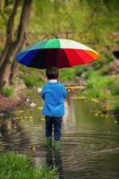 menino bonitinho, andando em uma lagoa na chuva
