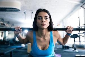 Attractive young woman working out with barbell photo