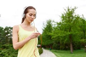 joven deportiva eligiendo música en el parque foto